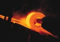 a large hot orange steel sheet is being rolled by a machine in a steel mill